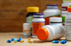 Medicine bottles and tablets on wooden desk